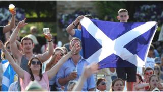 Fans of Andy Murray of Great Britain hold up a Scottish Saltire flag during his men's singles semi final match against Jerzy Janowicz of Poland on day eleven of the Wimbledon Lawn Tennis Championships at the All England Lawn Tennis and Croquet Club on July 5, 2013 in London, England