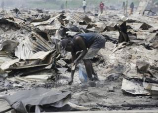 Residents salvage objects from the demolished houses that were set ablaze by government officials in Lekki, Lagos, Nigeria. Saturday, 12 November 2016