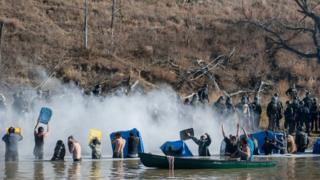 Police use pepper spray against people standing in the water of a river during a protest against the building of a pipeline on the Standing Rock Indian Reservation near Cannonball, North Dakota, Nov 2, 2016