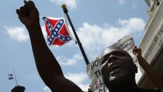 Man protests before a Confederate flag