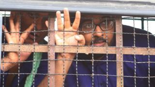 Serbest gazeteci Aung Naing Soe (sağda) 27 Kasım'da duruşma salonuna getirilirken.