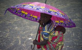 A child with a baby on her back sheltering under an umbrella at a refugee settlement in Palorinya in Uganda - Saturday 25 February 2017