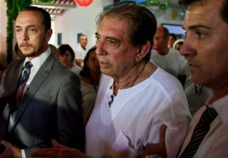 """Brazilian """"spiritual healer"""" Joao Teixeira de Faria escorted by two supporters on 12 December, 2018"""
