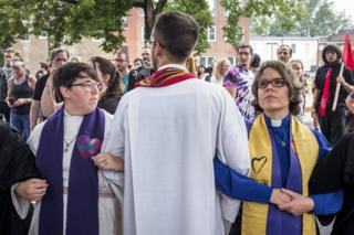 Clergy leaders lock arms at Emancipation park prior to the Unite the Right Rally on August 12, 2017 in Charlottesville