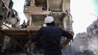 A member of the Syrian civil defence volunteers, known as the White Helmets, looks at a destroyed building following a reported air strike on the rebel-held town of Douma, on the eastern outskirts of the capital Damascus