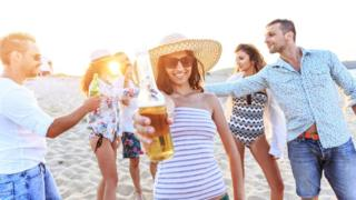 Holidaymakers on beach with drinks