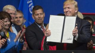 Donald Trump mostrando la orden ejecutiva.
