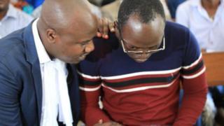 Kabendera akishauriana na wakili wake Jebra Kambole katika mahakama ya Kisutu