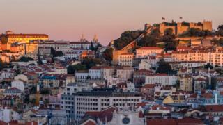 Imagem mostra vista geral de Portugal, com vários imóveis, bandeiras do país e o Castelo de São Jorge aparecendo