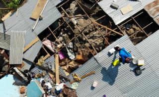 People on the roof of a collapsed building in Palu