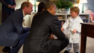 Britain's Prince George shakes hands with a kneeling Barack Obama, while the first lady and George's father, Prince William, look on.