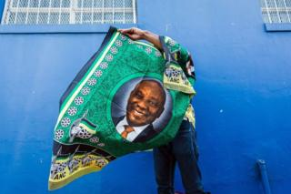 A street vendor sells regalia depicting South African President Cyril Ramaphosa outside the venue for the African National Congress (ANC) 107th anniversary celebrations at the Moses Mabhida Stadium in Durban on January 12, 2019.