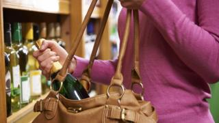 Woman slips bottle of wine into bag