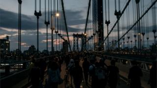 Protesters defy a curfew to walk over New York's Manhattan Bridge, 2 May 2020