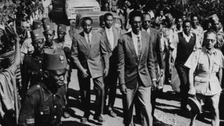King Kigeli V of Rwanda (front) is flanked by guards and crowds as he is escorted through a town, circa 1959.