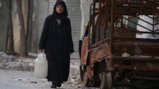 A woman carries a container of water as she walks past a burnt pick-up truck in a rebel-held area of Aleppo's Old City (14 November 2016)