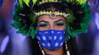 A dancer wearing a face mask poses for a portrait during a live streaming replacing the traditional Boi-Bumba folklore festival, cancelled amid the new coronavirus pandemic in Parintins, Amazonas state, Brazil, on June 27, 2020.