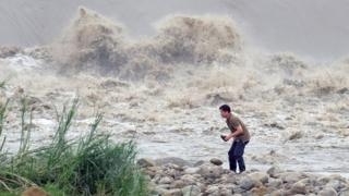 A local resident collects stones from the Xindian river after Typhoon Dujuan passed in the New Taipei City (29 Sept 2015)