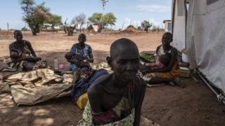 A cholera-stricken woman showing signs of malnutrition sits next to fellow patients (background) outside a temporary field hospital near the remote village of Dor in the Awerial county in south-central Sudan on April 28, 2017