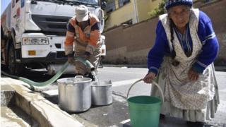 Mujer de la tercera edad cargando un balde de agua.