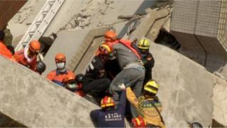 Rescuers carry a male survivor out from a building that collapsed, due to an earthquake, in Tainan, Southern Taiwan, in this February 7, 2016 still image taken from video.