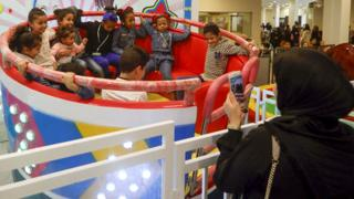 A woman taking a photo on her mobile of children in a teacup ride at an amusement arcade in Tajura, Libya - Friday 24 January 2020