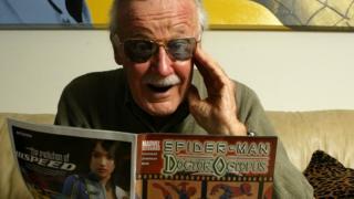 Stan Lee com uma revista de quadrinhos