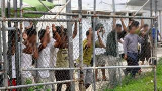 A file picture dated dated 21 March 2014 shows asylum seekers behind a fence at the Manus Island detention centre, in Papua New Guinea