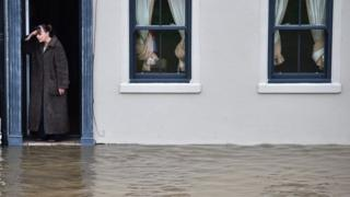 A resident watches flood waters outside her house