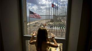 A child looks out a window from inside the newly opened US embassy overlooking the staging area on 14 August 2015