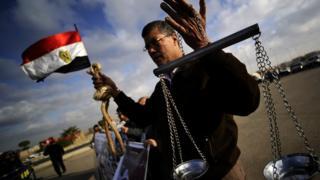 Un homme exhibe une corde d'exécution et une balance de la justice, lors du procès du président Hosni Moubarak en 2011.
