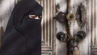 mulher uusando um niqab preto
