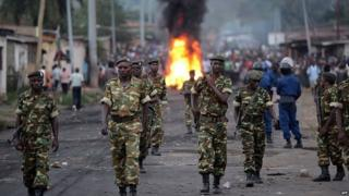 Burundian soldiers walk near a burning barricade erected by protesters - April 2015