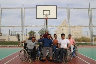 A group of men on the basketball pitch.