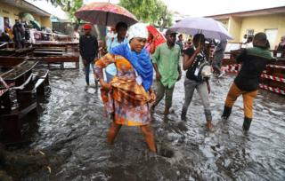 Voters wade through flood water at a polling station during the presidential election in Kinshasa, Democratic Republic of Congo, December 30, 2018