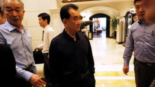 Kim Chang Son stands between his staff inside Metropole Hotel in Hanoi