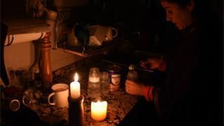 Жінка запалює свічки після того, як світло зникло в її будинку в столиці Уругваю Монтевідео