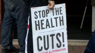 A protester's sign that reads: Stop the health cuts