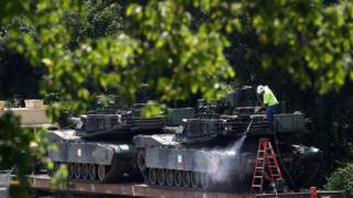 A worker washes one of two M1A1 Abrams tanks that are loaded on rail cars at a rail yard on 2 July in Washington, DC