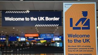 "A photo of the UK Border Control at an airport shows two signs, reading ""Welcome to the UK border"" and ""Welcome to the UK"", with warning about passport control"