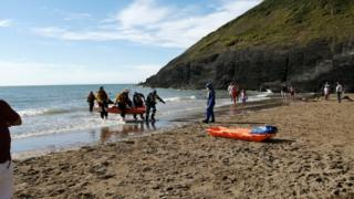 The casualty is taken out of the sea on a stretcher