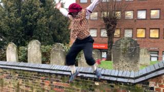 Nicholas Potts jumping the church wall at the end of his challenge near the Maddermarket Theatre in Norwich