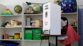 Mulher vota em cabine de votação no primeiro turno das eleições 2018