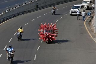 healthy fod for babies A man drives an auto-rickshaw depicting the coronavirus