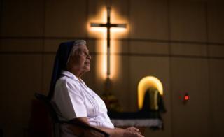 Gerard Fernandez, 81, é retratada de perfil dentro de convento, onde se vê um crucifixo na parede