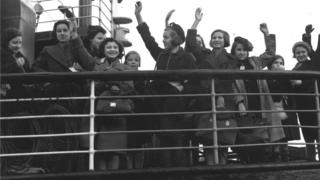 Children wave from the deck of a boat