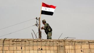 11 Temmuz'da çekilen bu fotoğrafta bir Suriyeli askerin Süveyda bölgesinin eteklerindeki bir binaya Suriye bayrağı astığı görülüyor.