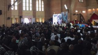Mourners inside the cathedral with Papa Wemba's coffin at the front