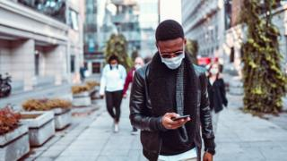 man wearing mask looking at phone