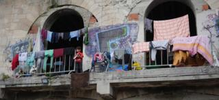 A very young boy stands on a balcony with no barrier or railing at the derelict building, surrounded by washing that has been hung out to dry